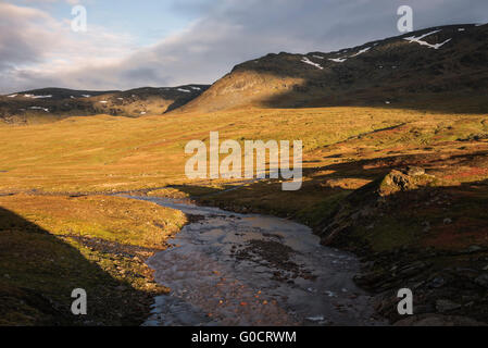 River flows through the scenic Syterskalet mountain valley near Viterskals hut, Kungsleden trail, Lapland, Sweden - Stock Image