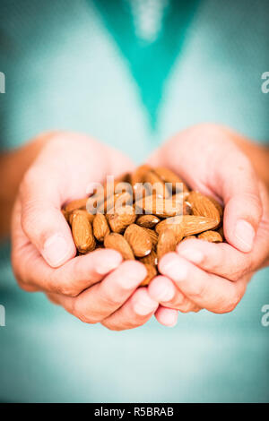 Woman holding almonds. - Stock Image