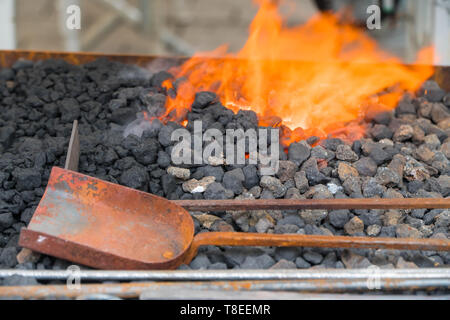 Farrier's furnace with flaming coals and forging tools - Stock Image