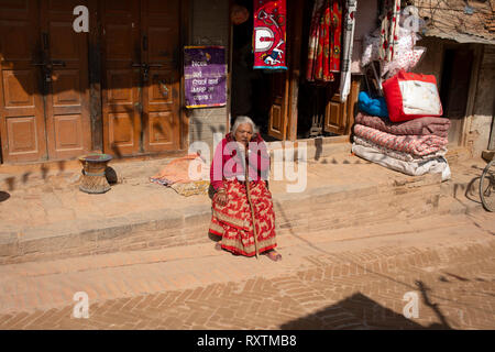 An elderly Nepali lady takes a rest by sitting on a wall. Bhaktapur, Nepal. - Stock Image