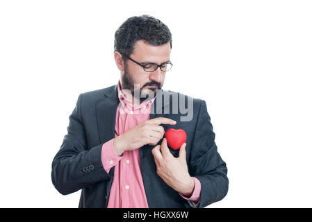 Man pulling out a red heart from the pocket of his suit - Stock Image