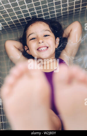 vertical photo of a playful beautiful little girl having fun and smiling lying in the tub and showing the feet while taking a bath in the bathtub, kid - Stock Image