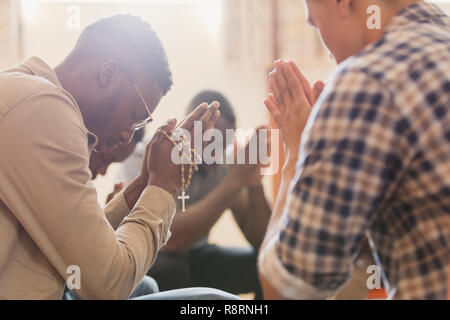 Men praying with rosary in prayer group - Stock Image
