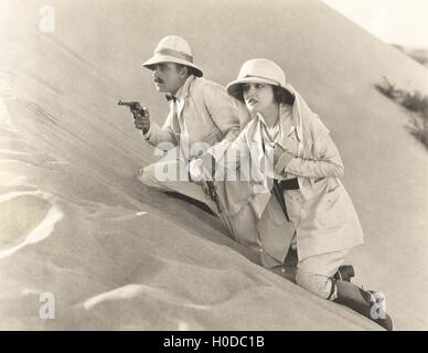 Armed couple climbing up sand dune - Stock Image
