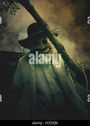 A scary evil scarecrow man is holding a stick with a monster burlap mask on his face for a nightmare halloween concept. - Stock Image