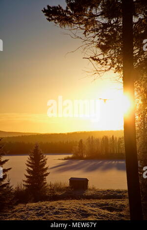 A wooden hut is standing at the shore of a frozen lake at sunset. - Stock Image