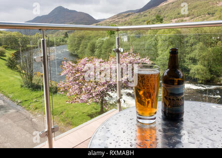 Glass of River Leven Blonde Ale, brewed in Kinlochleven on the balcony of the Highland Getaway Inn overlooking the River Leven, Kinlochleven, Scotland - Stock Image