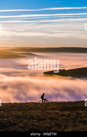 Sun setting over a fantastic Peak District mountain landscape. A biker makes its way through the hills and the fog. - Stock Image