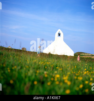 Exterior view of mother and child walking in a flowery meadow near the 15th Century White Church at Mwnt Cardiganshire in Wales UK  KATHY DEWITT - Stock Image