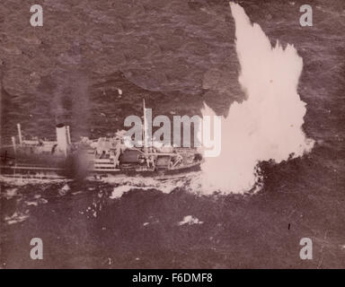 714. Merchant vessel attacked and bombed by the RAF Coastal Command Sunderland plane. Bombs burst around the ship. - Stock Image