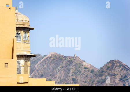 Stunning view of an ancient tower in the foreground and a blurred long wall on the top of a mountain in the background. Amber Fort, Amer, Jaipur. - Stock Image