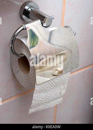 Toilet paper roll in holder on tiled wall - Stock Image