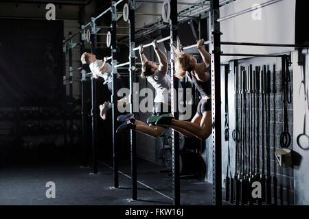 Three young adults training on wall bar in gym - Stock Image