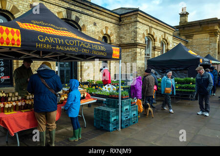 People enjoying spring sunshine in a sheltered corner of the Monthly Farmers Market by the station at Saltburn by the sea North Yorkshire - Stock Image