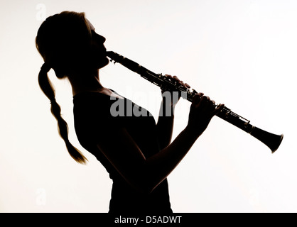 Female Musician Practices her Woodwind Technique on a Clarinet Photographed in silhouette - Stock Image