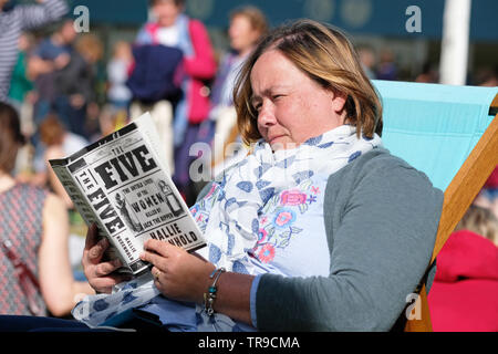 Hay Festival, Hay on Wye, Powys, Wales, UK - Friday 31st May 2019 - A visitor enjoys a break between events on the Festival lawns to read the new book by Hallie Rubenhold as the sun emerges on Friday afternoon. Photo Steven May / Alamy Live News - Stock Image