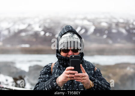 A lady takes a selfie by Godafoss Water Falls in Iceland, the water falls from a height of 12 metres over a width of 30 metres - Stock Image