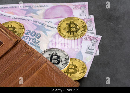 View of metal bitcoins in brown leather wallet and over Turkish Lira banknotes.Concept image for cryptocurrency - Stock Image