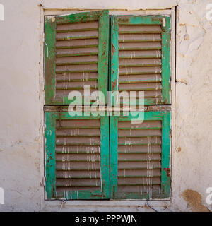 Old grunge window with closed green shutters on dirty bricks stone wall, Cairo, Egypt - Stock Image