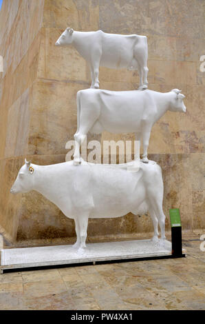 A sculpture of three cows on top of each other in the Maltese capital of Valletta - Stock Image
