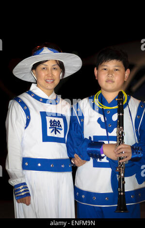 Falun Dafa (Falun Gong) members - mother and son - pose in their uniforms after taking part in a musical performance. - Stock Image