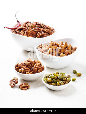 Bowls of a variety of nuts such as cashews pecans walnuts and pistachios with a white background cutout - Stock Image