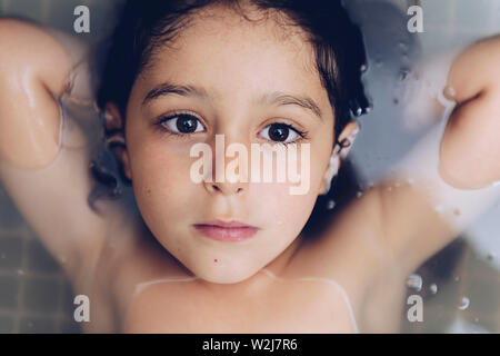 portrait of a happy pretty little girl lying in the tub while taking a bath in the bathtub, kids hygiene concept - Stock Image