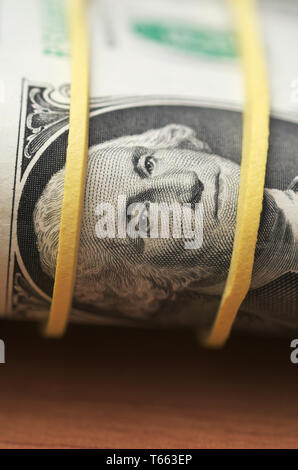 A roll of one dollar bills wrapped with a rubber band - Stock Image
