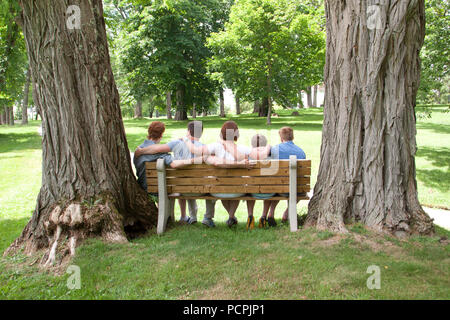 A lovely family of gingers sits together on a park bench viewed from the back - Stock Image