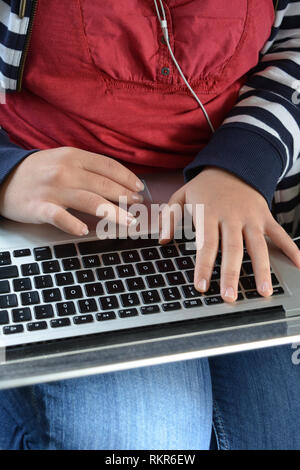 Millennial woman typing on a laptop keyboard, close up - Stock Image