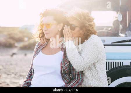 People traveling together - couple of caucasian curly friends women whispering at the ear some secrets with sunny sunset in backgorund - old vintage v - Stock Image