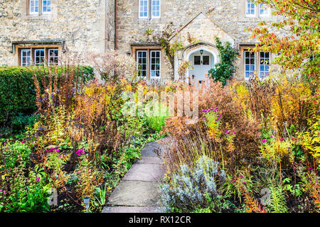 The autumnal front garden of a stone cottage in the Cotswolds, England. - Stock Image