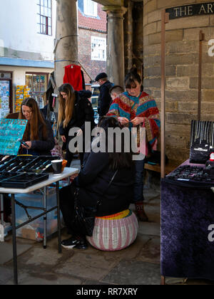 Hair Braiding being carried out  under the Old Town Hall in the Market Place in Whitby North Yorkshire - Stock Image