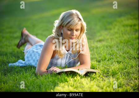 Girl in park reading - Stock Image