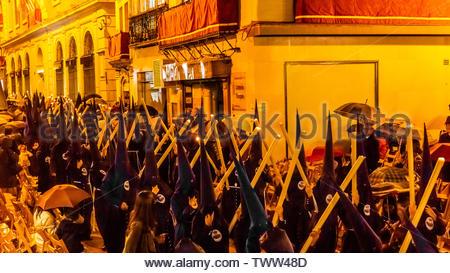 Hooded Penitents (Nazarenos) in the procession of the Brotherhood (Hermandad) El Baratillo, Holy Week (Semana Santa), Seville, Andalusia, Spain. - Stock Image