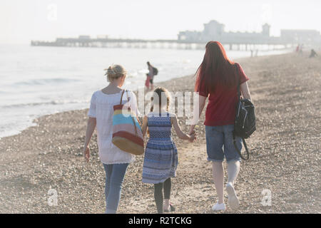 Lesbian couple and daughter walking on sunny beach - Stock Image