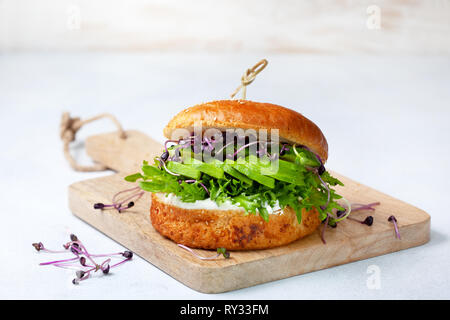 green burger with avocado, cucumber, cream cheese and micro greens on a cutting board - Stock Image