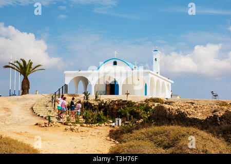 A family of tourists looking at the cave church at Agia Thekla church,Agia Napa, Cyprus October 2018 - Stock Image