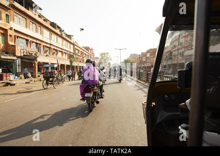 A rickshaw (also known as Tuc Tuc) driver is driving on the streets of Jaipur in India. - Stock Image