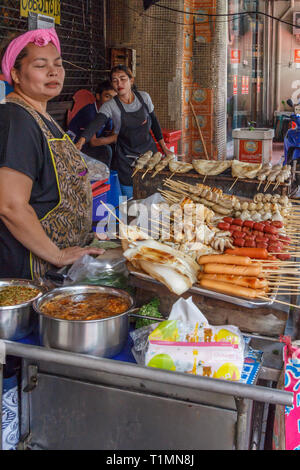 Bangkok, Thailand - 7th March 2017: Street food vendors selling barbecued sausages and squid in Chinatown, Most Thais eat street food. - Stock Image
