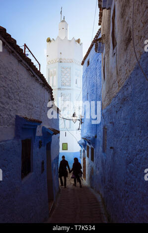 Chefchaouen, Morocco : A couple walks in a blue-washed alleyway under the minaret of a mosque in the medina. - Stock Image