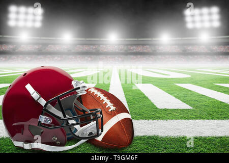 Close up of American football helmet and ball on stadium field with yard line markings and spotlight with blurred background and copy space. - Stock Image