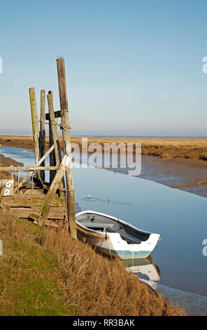 A white dinghy moored at the quayside at the North Norfolk harbour at Thornham, Norfolk, England, United Kingdom, Europe. - Stock Image