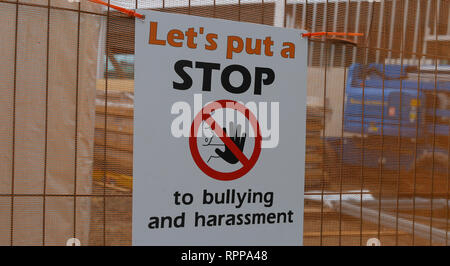 Warning sign on construction site stop bullying and harassment. - Stock Image