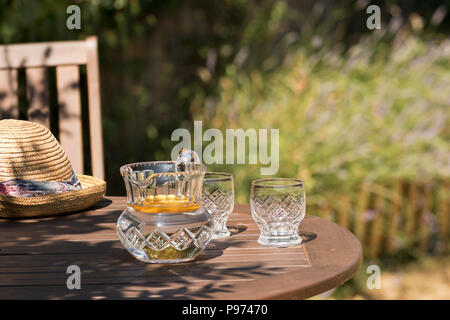 Antique cut glass water jug and two glasses in a summer garden on a sunny day. - Stock Image