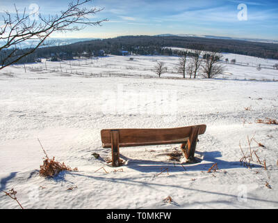Wooden bench  on hill covered in snow with a Christmass wintery and snowy background - Stock Image