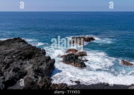 Atlantic Ocean waves breaking over the edge of the volcanic lava field at Mirador Playa Los Guirres, (Playa Nueva), La Palma, Canary Islands, Spain - Stock Image
