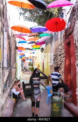 Cartagena Colombia Old Walled City Center centre Getsemani Callejon Angosto Calle 27 narrow street hanging colorful umbrellas installation Hispanic ma - Stock Image