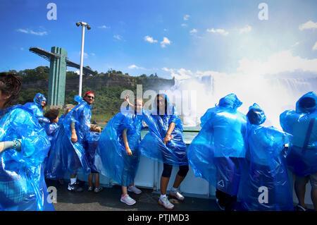Niagara Falls, USA – August 29, 2018: Happy group tourists in blue raincoats on boat tour watching Niagara Falls - Stock Image