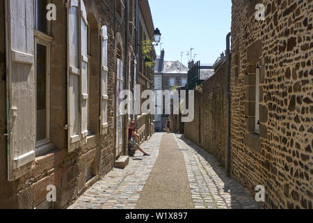 A man on a smartphone and a woman walking towards camera in a small narrow street in Fougères, Brittany, France - Stock Image